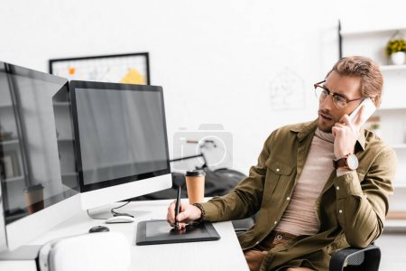 Photo for 3d artist talking on smartphone and using graphics tablet and computers at table in office - Royalty Free Image
