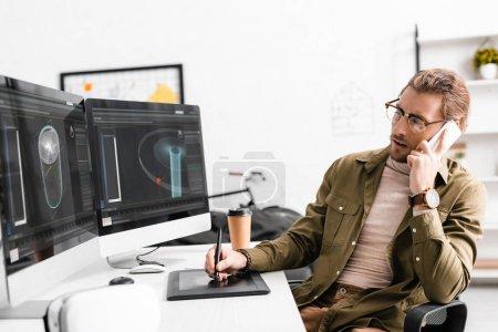 Photo pour Un artiste 3d parle sur un smartphone tout en créant un design 3d sur un ordinateur de bureau - image libre de droit