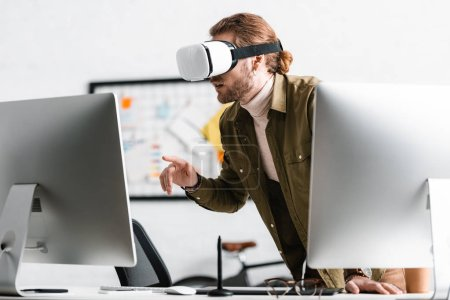 3d artist using vr headset near computers on table in office