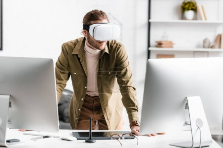 Photo for Digital designer in virtual reality headset standing near computers and graphics tablet on table - Royalty Free Image