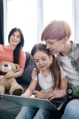 Photo pour Concentration sélective de la femme étreignant sa fille tout en utilisant un ordinateur portable près du parent avec un ours en peluche sur le canapé - image libre de droit