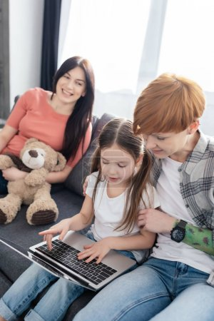 Photo pour Concentration sélective de la mère en utilisant un ordinateur portable avec sa fille près d'un parent souriant avec un ours en peluche sur le canapé à la maison - image libre de droit
