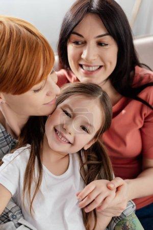 Photo pour Enfant joyeux souriant à la caméra près de parents de même sexe sur le canapé - image libre de droit