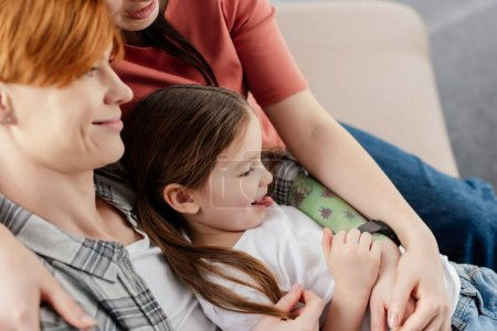 Photo pour Side view of smiling same sex couple hugging daughter sticking out tongue on couch - image libre de droit