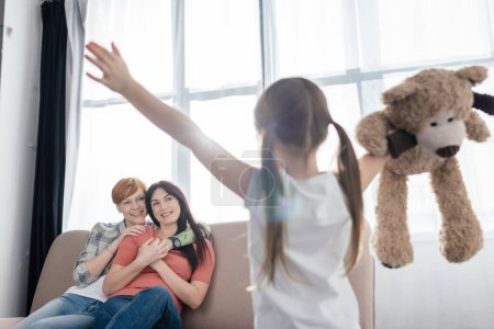 Photo pour Selective focus of smiling mothers looking at daughter with teddy bear in living room - image libre de droit