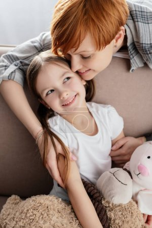 Photo for Smiling mother hugging daughter with soft toys on sofa in living room - Royalty Free Image