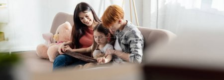 Photo for Selective focus of child playing with teddy bear near smiling parents on sofa in living room, panoramic shot - Royalty Free Image
