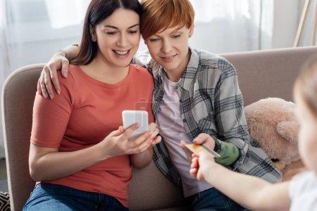 Foto de Enfoque selectivo de las madres que utilizan teléfonos inteligentes y la hija que dan tarjeta de crédito en el salón. - Imagen libre de derechos