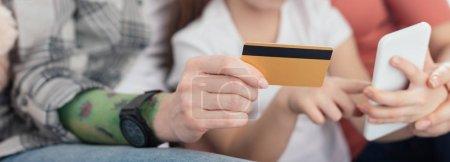 Foto de Vista cruzada de padres del mismo sexo usando smartphone y tarjeta de crédito con hija, tiro panorámico. - Imagen libre de derechos