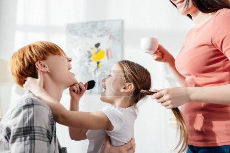Photo pour Vue latérale de parents du même sexe souriants riant avec leur fille tenant un peigne dans le salon - image libre de droit