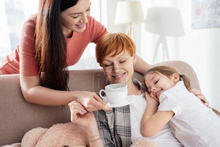 Photo pour Une femme souriante donne du café à un parent serrant sa fille heureuse sur un canapé - image libre de droit