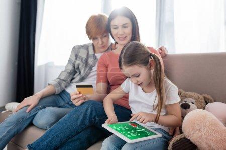 Foto de Joven usando tableta digital con aplicación de e-salud en pantalla cerca de madres con tarjeta de crédito en casa. - Imagen libre de derechos