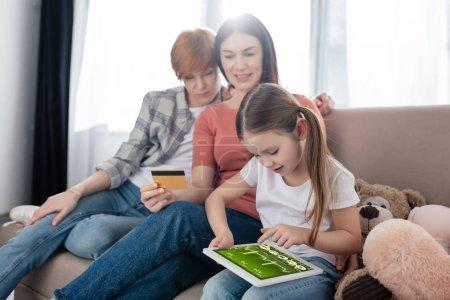 Foto de Niños que usan tableta digital con aplicación de e-salud en la pantalla cerca de padres del mismo sexo con tarjeta de crédito. - Imagen libre de derechos