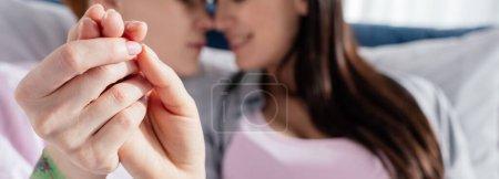 Photo pour Foyer sélectif de même sexe couple tenant la main sur le lit, panoramique coup - image libre de droit