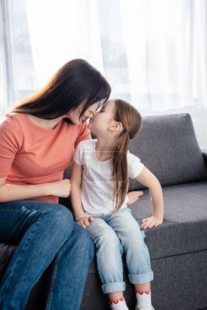 Photo pour Mère embrasser fille sur canapé dans le salon - image libre de droit
