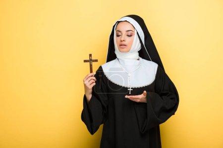 Photo pour Belle jeune nonne montrant croix sur jaune - image libre de droit