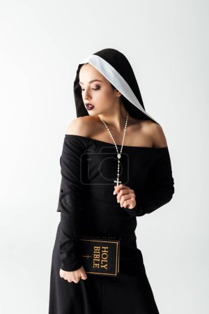 Photo pour Nonne sensuelle en robe noire tenant la bible isolée sur gris - image libre de droit