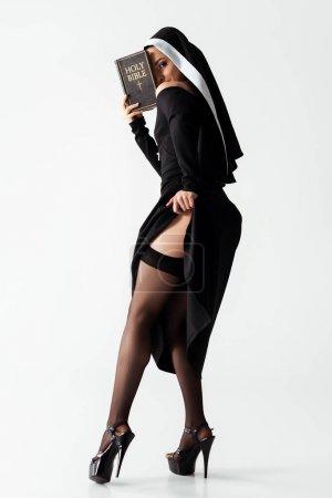 Photo pour Jolie religieuse passionnée en robe noire et bas lisant la bible sur le gris - image libre de droit