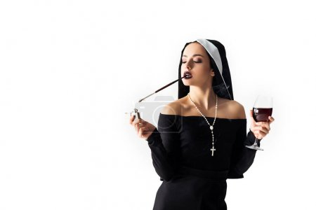 Photo for Seductive nun with lighter and glass of wine smoking a cigarette in mouthpiece isolated on white - Royalty Free Image