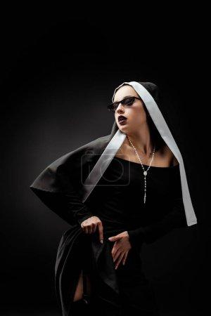 Photo pour Jeune religieuse sexy en robe noire et lunettes de soleil, sur noir - image libre de droit