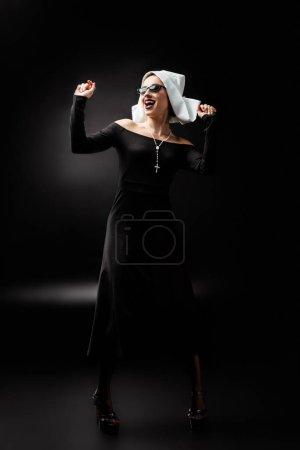 Photo pour Sexy excité danse de la religieuse en robe noire et lunettes de soleil, sur noir - image libre de droit