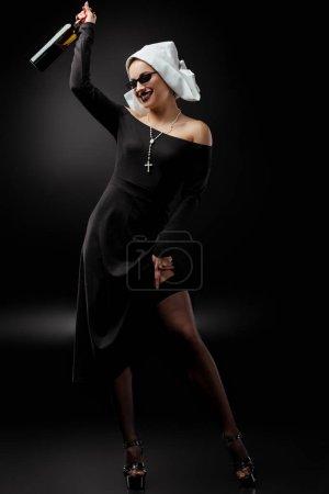 Photo pour Jolie religieuse sexy dans des lunettes de soleil tenant une bouteille de vin sur gris - image libre de droit