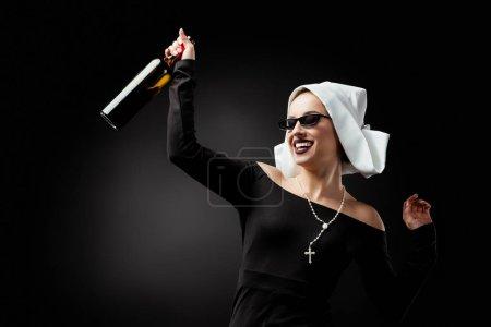 Photo pour Jolie religieuse souriante dans des lunettes de soleil tenant une bouteille de vin sur gris - image libre de droit