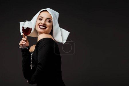 Photo pour Une religieuse joyeuse et sexy tenant un verre de vin rouge isolé sur gris - image libre de droit