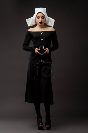 Photo pour Jolie religieuse attentionnée tenant un verre de vin rouge sur fond gris - image libre de droit