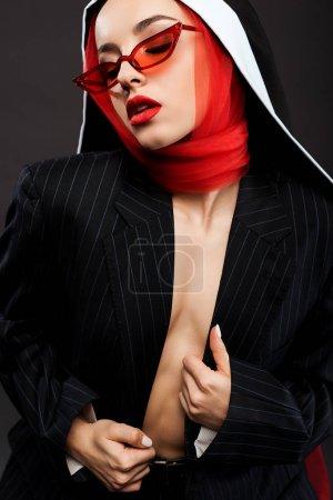 Foto de Atractivo nun sexy de moda que presenta en traje negro, gafas de sol rojas y bufanda, aislado en gris. - Imagen libre de derechos