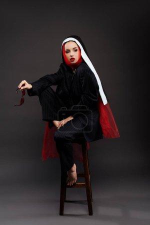 Photo pour Nonne sexy et stylisée aux pieds nus en costume noir et écharpe rouge avec lunettes de soleil, sur gris - image libre de droit