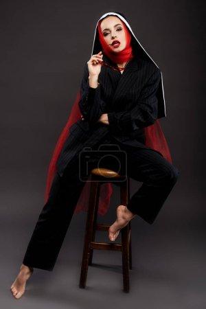 Foto de Descalzo de moda sexy nun posando en traje negro y pañuelo rojo con gafas de sol, en gris. - Imagen libre de derechos