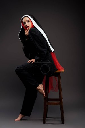 Photo pour Nu-pieds sexy à la mode posant en costume noir et foulard rouge, sur gris - image libre de droit