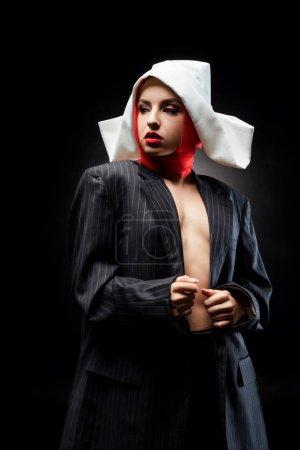 Foto de Atractivo desnudo sexy nido posando en traje negro y pañuelo rojo, aislado en negro. - Imagen libre de derechos