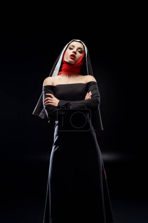 Foto de Beautiful sexy nun posing in black dress and red scarf standing with crossed arms, isolated on black - Imagen libre de derechos