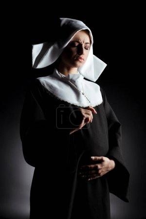 Photo pour Inquiet nonne enceinte tenant croix et toucher le ventre sur gris - image libre de droit