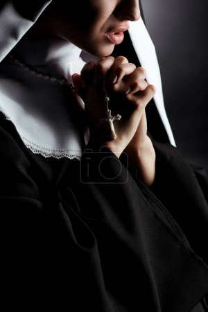 Photo pour Cropped view of worried young nun praying with cross on grey - image libre de droit