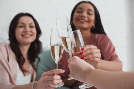 Photo pour Vue recadrée de femmes afro-américaines et caucasiennes souriantes et cliqueteuses avec des verres à champagne dans la chambre - image libre de droit