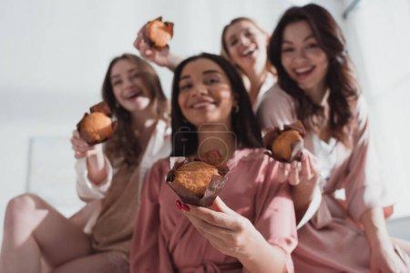 Foto de Enfoque selectivo de mujeres multiculturales con muffins, sonriendo y mirando la cámara en el partido bachelorette. - Imagen libre de derechos