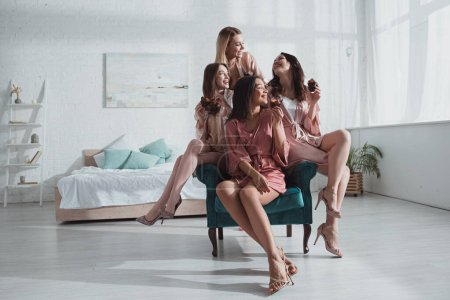 Happy multicultural women with muffins in armchair together in room at bachelorette party