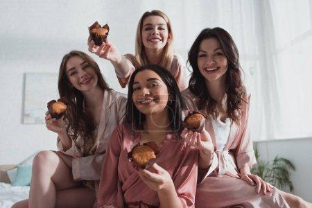 Photo pour Concentration sélective des femmes multiculturelles souriant et montrant des muffins dans la chambre à la fête de célibataire - image libre de droit