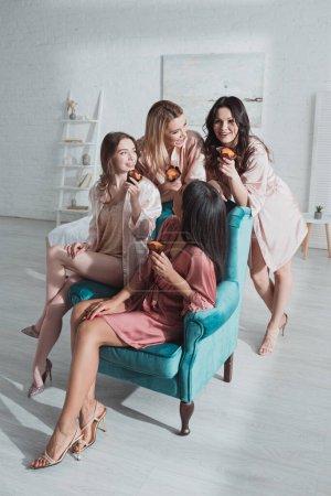 Photo pour Concentration sélective d'amis multiculturels heureux avec des muffins dans le fauteuil dans la chambre à la fête de célibataire - image libre de droit