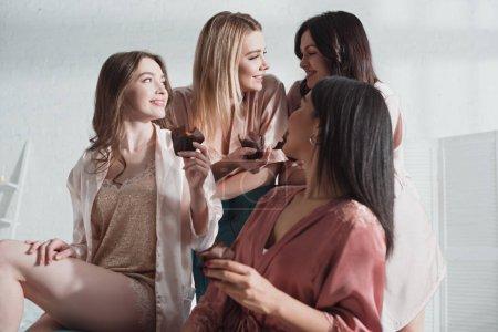 Photo pour Vue en angle bas de femmes multiculturelles avec des muffins se regardant et souriant dans la chambre au enterrement de vie de jeune fille - image libre de droit