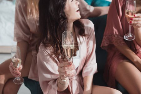 Photo pour Vue recadrée d'amis multiculturels heureux avec des verres de champagne à la fête de célibataire dans la chambre - image libre de droit
