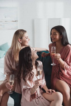 Photo pour Concentration sélective des femmes multiculturelles avec verres à champagne à la fête de célibataire dans la chambre - image libre de droit