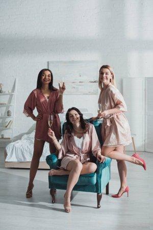 Photo pour Focus sélectif de femmes multiethniques heureuses avec des verres de champagne souriant et regardant la caméra dans la chambre - image libre de droit