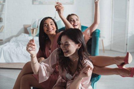 Photo pour Selective focus of happy multiethnic women raising champagne glasses in arm chair at bachelorette party - image libre de droit