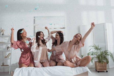 Photo pour Femmes multiculturelles heureuses et excitées avec les mains dans l'air sur le lit avec des plumes dans la chambre au enterrement de vie de jeune fille - image libre de droit