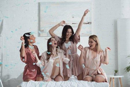 Photo pour Heureuses et excitées femmes multiethniques avec les mains dans l'air sur le lit avec des plumes dans la chambre au enterrement de vie de jeune fille - image libre de droit
