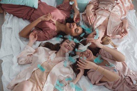 Photo pour Vue du dessus des femmes multiethniques heureuses souriantes et allongées sur le lit avec des plumes à la fête de célibataire - image libre de droit